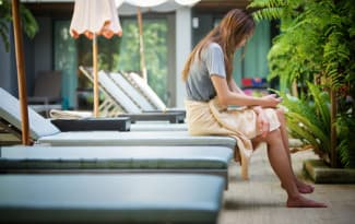 asia-woman-using-a-smart-phone-on-lounger-near-swimming-pool-in-hotel-krabi-thailand